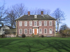 A two-storey brick-built mansion in its own well-kept garden of green grass. The ground floor has six windows – three on each side of a wooden front door. The second floor has seven windows. The house has a grey slate roof surmounted by two small brick chimneys. Behind the house are leafless trees and behind those, a clear blue sky.