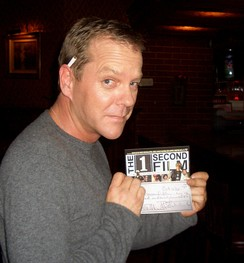 Sutherland holding his cheque for The 1 Second Film, 2006