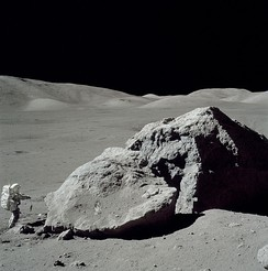 Apollo 17 astronaut Harrison Schmitt standing next to a boulder at Taurus-Littrow.