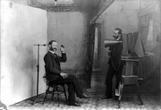 In this 1893 multiple-exposure trick photo, the photographer appears to be photographing himself. It satirizes studio equipment and procedures that were nearly obsolete by then. Note the clamp to hold the sitter's head still.