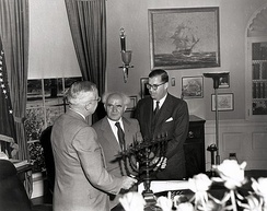 U.S. President Harry S. Truman in the Oval Office, receiving a Menorah as a gift from the Prime Minister of Israel, David Ben-Gurion (center). To the right is Abba Eban, the Ambassador of Israel to the United States.