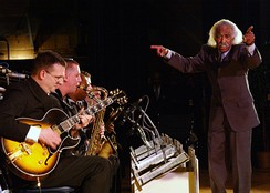 A conductor, Gerald Wilson, leads a jazz big band