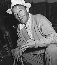 A man wearing a grey sweater and a fedora squats near an open box, holding a small canvas bag.