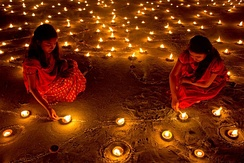 Lighting candle and clay lamp in their house and at temples during Diwali night