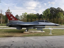 An F-16B on display at the Aviation Challenge campus of the U.S. Space & Rocket Center in Huntsville, AL; dorsal fin has an acknowledgement to Tuskegee Airmen.