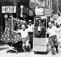 Men pulling carts of women's clothing in Garment District, New York, 1955