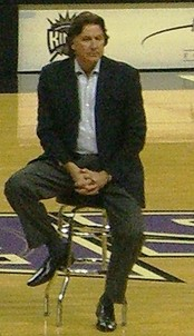 A man wearing a suit sits on a stool at an arena.