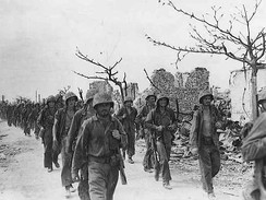 Marines march through Garapan, July 1944