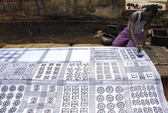 Anthony Boakye prints an adinkra cloth with a calabash stamp in Ntonso, Ashanti.