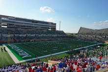 A marching band performs on the field of a football stadium.