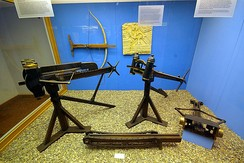 Reproductions of ancient Greek artillery, including catapults such as the polybolos (to the left in the foreground) and a large, early crossbow known as the gastraphetes (mounted on the wall in the background)