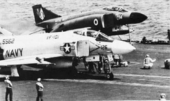 An F-4J of the U.S. Navy (foreground), alongside an F-4K of the Fleet Air Arm (background) wait to be catapulted from the USS Independence, March 1975; one of the major differences can be seen by the higher degree of the British aircraft's extendable nose wheel. Both variants were eventually used by the RAF
