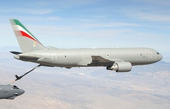 A mostly-gray KC-767, with refueling probe extended, transferring fuel to a B-52 in the left-bottom hand corner