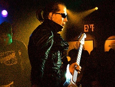 "Link Wray, pictured in 1993, who helped pioneer the use of guitar power chords and distortion as early as 1958 with the instrumental, ""Rumble"", has been cited as an early influence on garage rock."