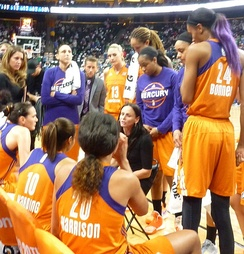 Coaches Julie Hairgrove, Todd Troxel (left to right) and head coach Sandy Brondello (seated) in a timeout during the 2016 WNBA semifinals.