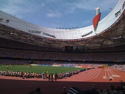 Inside Beijing National Stadium during the Games. Olympic cauldron in background.