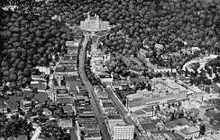Aerial view of Hot Springs after 1925 along Central Avenue. The base of Hot Springs Mountain is in top right, behind Bathhouse Row. Part of West Mountain is on the left. The southwest edge of North Mountain is behind the Arlington Hotel at top.