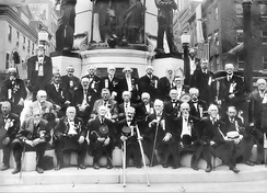 1911 photograph of the 50th Reunion of the Allen Infantry, Pennsylvania Militia at the Soldier's and Sailors Monument looking westward. The group's commander, Captain Thomas Yeager, appears to be sitting in the center of the front row of the veterans, holding a GAR cap between crutches.
