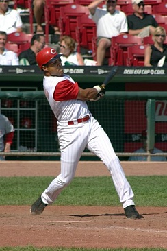 Barry Larkin follows through after a hit, wearing a Cincinnati Reds uniform