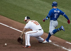 Kevin Pillar (right) beats out a throw to first base.