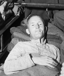 "William Joyce, who was ""Lord Haw-Haw"" to British wartime listeners, now under arrest, lies in an ambulance under armed guard before being taken from British Second Army Headquarters to a hospital."