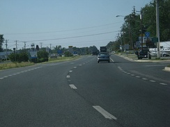 A divided highway curves to the right. In the median are signs indicating the road is entering Delaware.