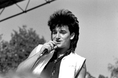 A black and white image of a light-skinned man singing into a microphone. He is visible from the chest up and wears a sleeveless black shirt with an opened sleeveless white vest overtop. A small cross is worn around his neck. His black hair is styled into a mullet. The man looks past the camera to the left. A mixture of trees and sky are visible in the background.