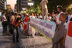 "A crowd of protestors along a street displays a banner reading ""Human Rights Abuse Cannot Co-exist with Beijing Olympics"". Near the centre of the image, a photographer holds a camera level with the banner while looking through the viewfinder."