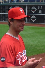 "A man in a red baseball jersey with ""Phillies"" and red baseball cap with a white ""P"" on the front reaches his hand toward an unseen person."