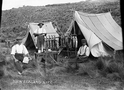 "Three men at their camp site displaying a catch of rabbits and fish. A marginal note reads ""New Zealand Life""."