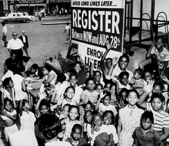 A group of African-American children gather around a sign and booth to register voters. Early 1960s.