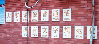 A school slogan asking elementary students to speak Standard Chinese is annotated with pinyin, but without tonal marks.