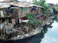 A multi-family shack in a riverside shantytown, Jakarta, Indonesia.