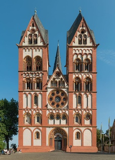 Limburg Cathedral, Germany. The facade, c. 1200, with polychrome plaster, follows the paired-tower model found at several Rhineland churches. The rose window has plate tracery and the spires are Rhenish helms.
