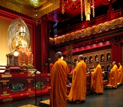 Buddhist adepts wearing saffron-coloured robes, pray in the Hundred Dragons Hall, Buddha Tooth Relic Temple and Museum, Singapore.