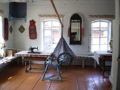 Внутреннее убранство старообрядческого дома. Этнографический музей народов Забайкалья.Раскрашенные лавки вдоль стен, зеркало с полотенцем, красный угол, большой и прямой стол, крашеные полы, колыбель на очепе.