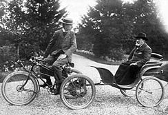 De Dion-Bouton tricycle towing a passenger in a carriage