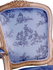 A photo of toile de jouy fabric on a French-reproduction-style chair