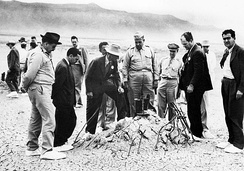 Major General Leslie Groves and Robert Oppenheimer at the Trinity shot tower remains a few weeks later. The white overshoes were to prevent the trinitite fallout from sticking to the soles of their shoes.