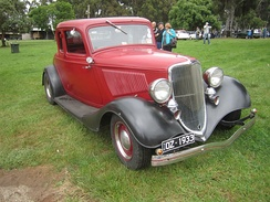1933 Ford Model B Standard 5 Window Coupe. This car has incorrect wheels. Painted window frame indicates a Standard. Twin chromed horns and cowl lamps were included on  Deluxes, and proved to be a popular option for Standard models.
