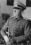 The head and shoulders of a man sitting, shown in semi profile. He wears a beaked cap and a military uniform, and an Iron Cross displayed at the front of his uniform collar. His left hand is gloved and he is holding the hilt of a saber in both hands. His facial expression is a determined; his head is pointed to the right of the camera.