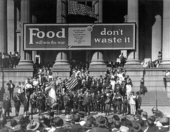 "Liberty Loan drive in front of City Hall, New Orleans. On City Hall is a banner reading ""Food will win the war—don't waste it""."