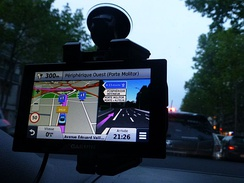 A personal navigation assistant GPS receiver in a car, which can give driving directions to a destination.