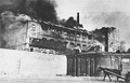 Factory burning during the Warsaw Ghetto Uprising; identified by Yad Vashem as view from the Aryan side. Gliniana St. near the cemetery. On the left is Okopowa St. and at the front is the ghetto walls.[16]