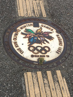 Stylized manhole cover displaying the Nagano Olympics emblem, with tactile paving