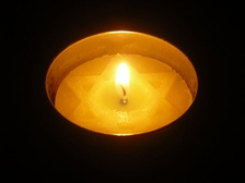 A lit Yom HaShoah Yellow Candle