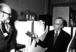 Senator Mathias exhibits his grip strength with a hand dynamometer during a tour of the Gerontology Research Center testing laboratories of the National Institutes of Health, 1980.