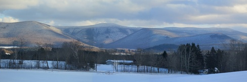 "The Mount Greylock massif seen from the west in winter, with the deep valley known as ""The Hopper"" directly below the summit"