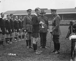 A black and white photo of a rugby field in which three men in military uniform, one of whom is King George V, present a silver trophy to a rugby player dressed in black kit. Behind in a line are the rest of the team.