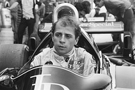 A black and white photograph of a man sitting inside a stationary racing car without a racing helmet but in racing overalls